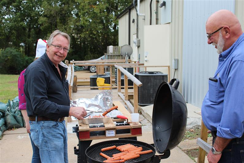 Mr. Herbert getting hot dogs off the grill